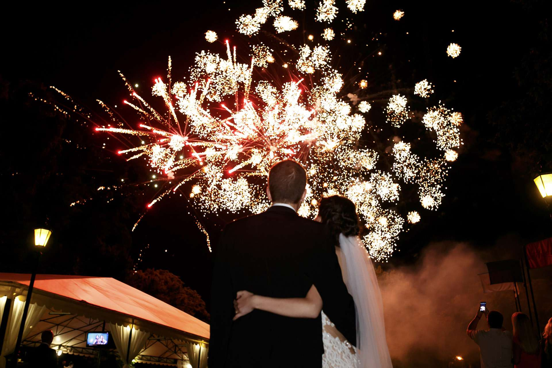 Happy hugging bride and groom watching beautiful colorful fireworks for weddings in night sky